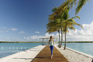 Young woman strolling on pier, Providenciales, Turks and Caicos Islands, Caribbean - ISF15085