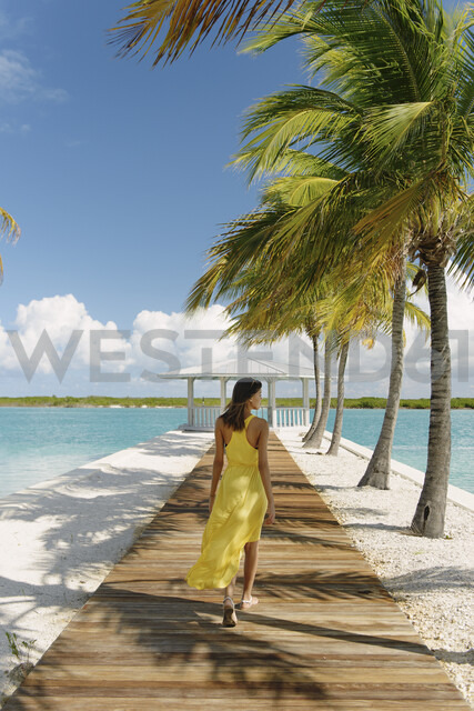 Young woman strolling on beach pier, Providenciales, Turks and Caicos Islands, Caribbean - ISF15088