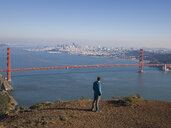 Young male tourist looking at Golden gate bridge, San Francisco, California, USA - ISF15094