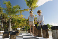 Brother and sister playing giant chess, Providenciales, Turks and Caicos Islands, Caribbean - ISF15106