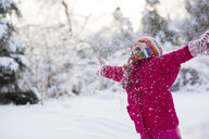 Young girl shouting and throwing snow mid air - ISF15124