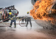 Firemen spraying water on simulated aircraft fire at training facility - CUF37901