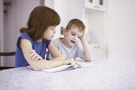 Girl reading book with brother at kitchen table - CUF37928