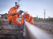 Railway maintenance workers using digital tablet to inspect track - CUF37982