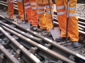 Railway maintenance workers standing with tools on track, low section - CUF37988