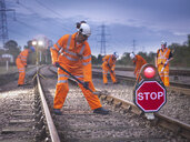 Railway maintenance workers on track with stop sign at night - CUF37994