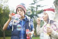 Siblings blowing bubbles in garden - CUF38030