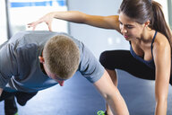 Couple helping each other in gym - ISF15151