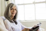 Portrait of attractive senior woman reading magazine - ISF15178