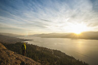 Male hiker watching sunset over Okanagan Lake, Naramata, British Columbia, Canada - ISF15253