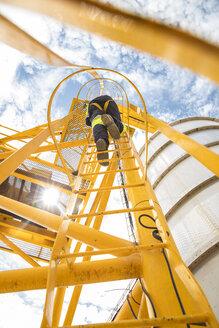 Worker climbing up ladder at tank - ZEF15751