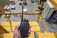 Hand holding walkie talkie on top of a crane on construction site - ZEF15757