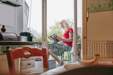 Pregnant woman sitting on balcony looking at photo book - RHF02031