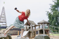 Happy pregnant woman balancing on a rock on playground - RHF02040