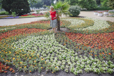 Pregnant woman standing amidst blooming flowers in park - RHF02052