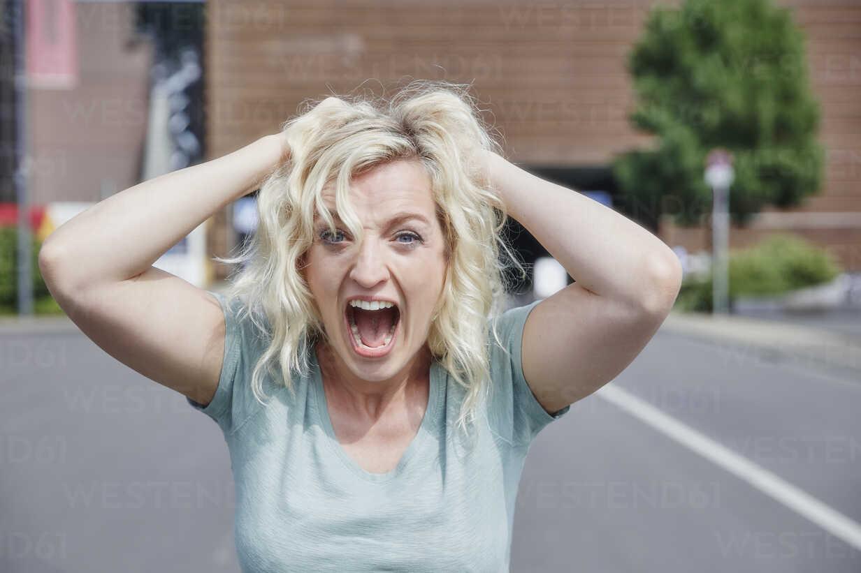 Portrait of screaming woman pulling her hair - RHF02067 - Rainer Holz/Westend61