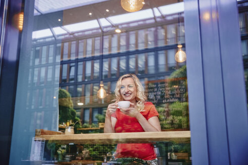Smiling blond woman drinking coffee in a cafe - RHF02070