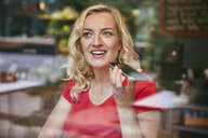 Portrait of happy blond woman using smartphone in a cafe - RHF02073