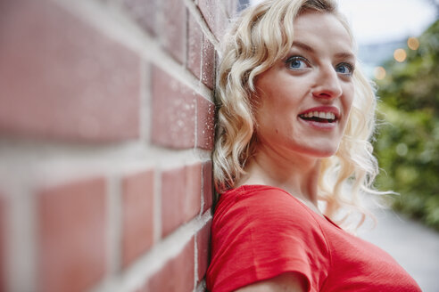 Portrait of blond woman outdoors leaning against a brick wall - RHF02079