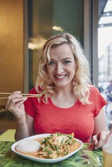 Portrait of smiling blond woman eating vegetarian Asian dish - RHF02082