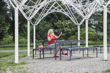 Smiling pregnant woman sitting on a park bench taking a selfie with a tablet - RHF02085