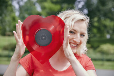 Portrait of happy woman holding a heart-shaped vinyl record outdoors - RHF02088