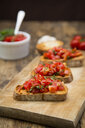 Bruschetta with tomato and basil on wooden board, close up - LVF07176