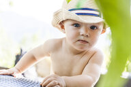 Portrait of curious baby boy wearing straw hat - TCF05503