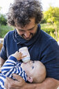 Father watching his baby boy drinking - TCF05515