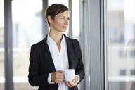 Businesswoman in office with cup of coffee  looking out of window - RBF06357