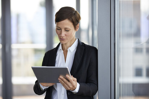 Businesswoman using tablet at the window in office - RBF06360