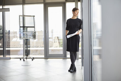 Businesswoman standing in office looking out of window - RBF06378