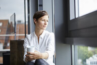 Businesswoman sitting in office with cup of coffee looking out of window - RBF06381
