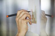 Hand drawing bar charts on paper at glass pane - RBF06384