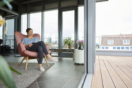 Woman sitting in armchair at home with tablet looking out of balcony door - RBF06387