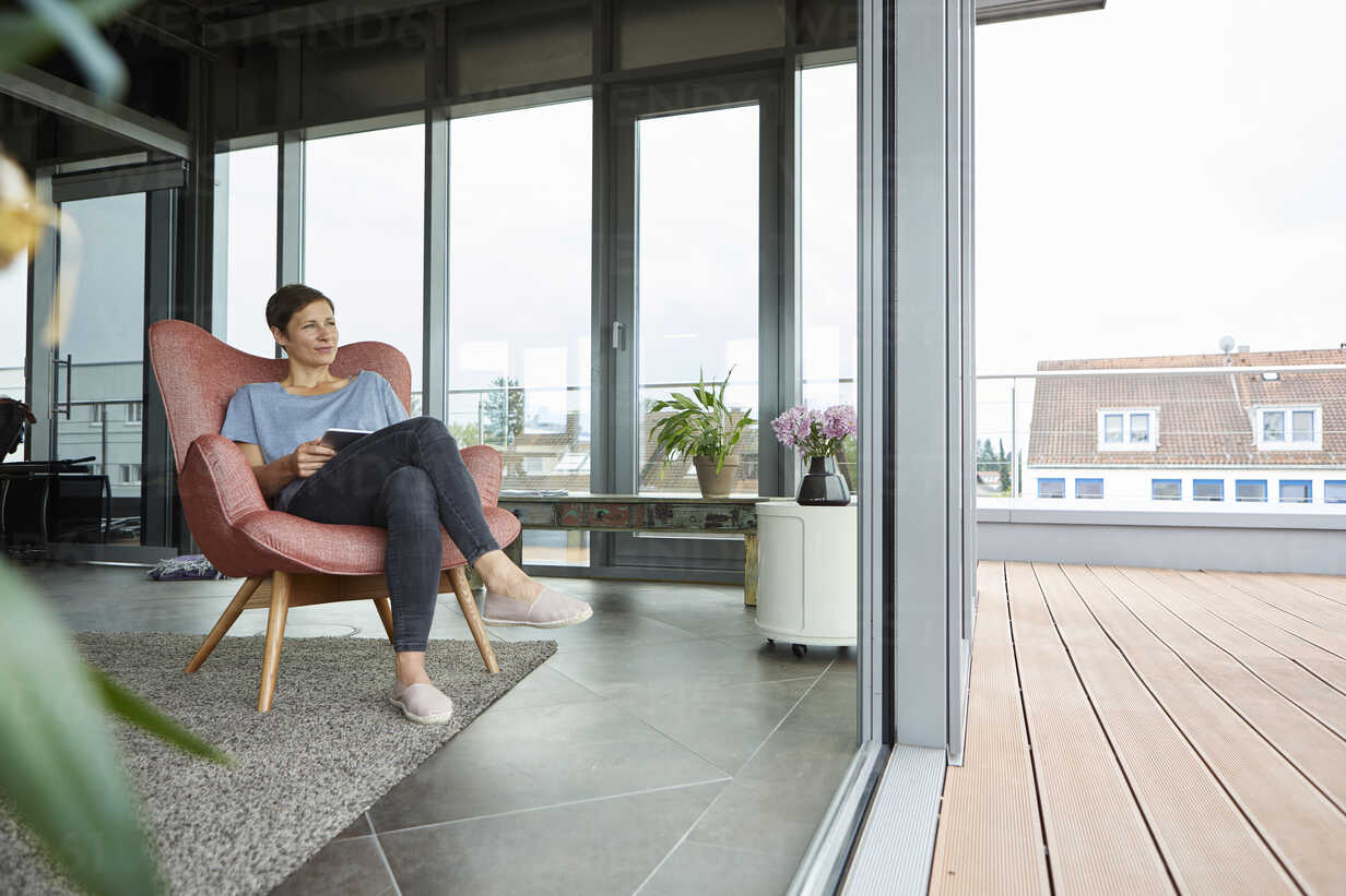 Woman sitting in armchair at home with tablet looking out of balcony door - RBF06387 - Rainer Berg/Westend61