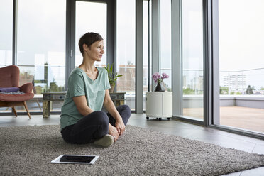 Woman sitting on the floor at home with tablet looking out of balcony door - RBF06390