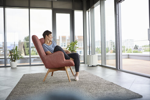 Woman sitting in armchair at home looking out of balcony door - RBF06393