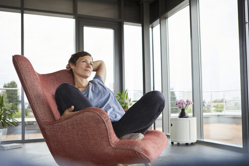 Woman sitting in armchair at home relaxing - RBF06396