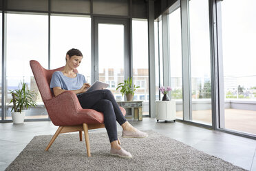 Woman sitting in armchair at home using tablet - RBF06399