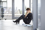 Overstressed businesswoman sitting on the floor in office - RBF06402