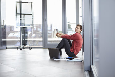 Businesswoman sitting on the floor in office with laptop and documents - RBF06405