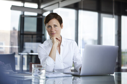 Portrait of confident businesswoman sitting at glass table in office with laptop - RBF06408