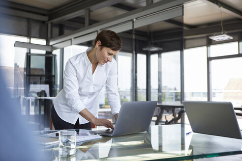 Businesswoman standing at glass table in office using laptop - RBF06411