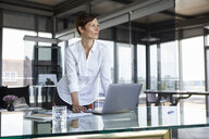 Businesswoman standing at glass table in office with laptop looking sideways - RBF06414
