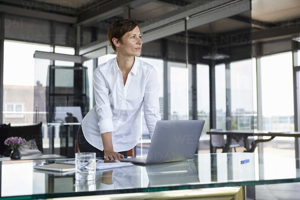 Businesswoman standing at glass table in office with laptop looking sideways - RBF06414 - Rainer Berg/Westend61