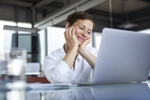 Smiling businesswoman sitting at glass table in office looking at laptop - RBF06417