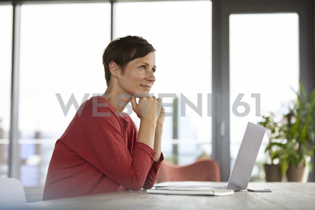 Smiling woman sitting at table at home using laptop - RBF06420 - Rainer Berg/Westend61