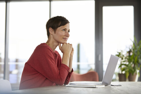 Smiling woman sitting at table at home using laptop - RBF06420