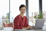 Portrait of smiling woman sitting at table at home using laptop - RBF06423